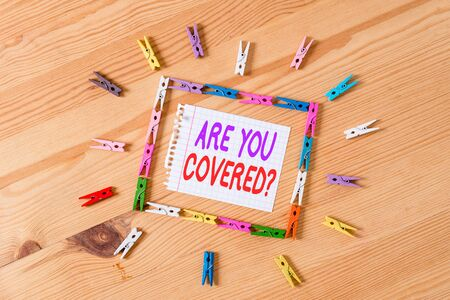 Handwriting text writing Are You Covered Question. Conceptual photo asking showing if they had insurance in work or life Colored clothespin papers empty reminder wooden floor background office Foto de archivo - 130032529