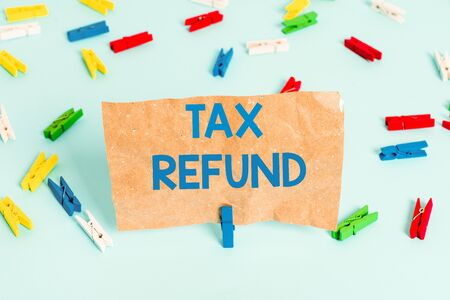 Text sign showing Tax Refund. Business photo text refund on tax when the tax liability is less than the tax paid Colored clothespin papers empty reminder blue floor background office pin Imagens