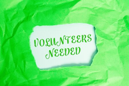 Text sign showing Volunteers Needed. Business photo text need work or help for organization without being paid Green crumpled ripped colored paper sheet centre torn colorful background Reklamní fotografie