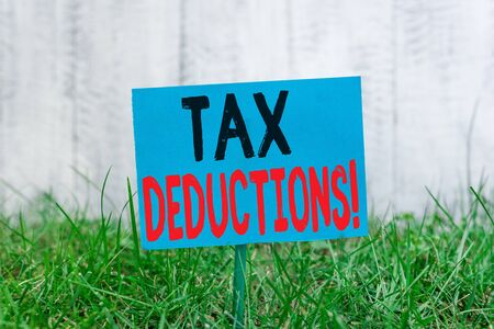 Handwriting text Tax Deductions. Conceptual photo reduction income that is able to be taxed of expenses Plain empty paper attached to a stick and placed in the green grassy land
