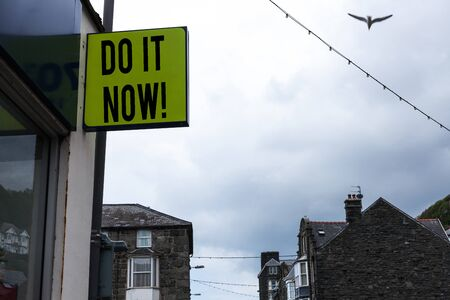 Writing note showing Do It Now. Business concept for not hesitate and start working or doing stuff right away Green ad board on the street with copy space for advertisement 写真素材