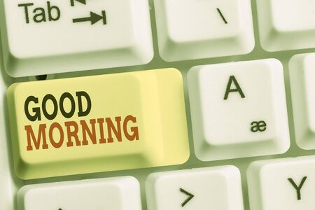 Handwriting text Good Morning. Conceptual photo A conventional expression at meeting or parting in the morning White pc keyboard with empty note paper above white background key copy space Фото со стока
