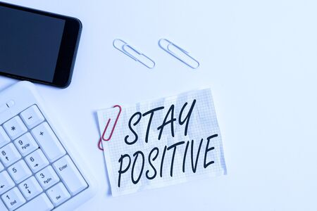 Text sign showing Stay Positive. Business photo showcasing Engage in Uplifting Thoughts Be Optimistic and Real White pc keyboard with empty note paper above white background and mobile phone