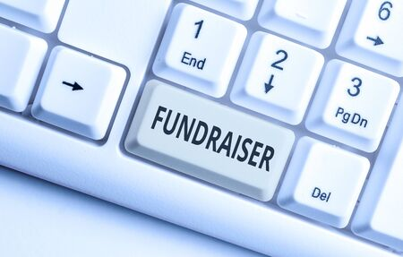 Text sign showing Fundraiser. Business photo showcasing demonstrating whose job or task is seek financial support for charity White pc keyboard with empty note paper above white background key copy sp