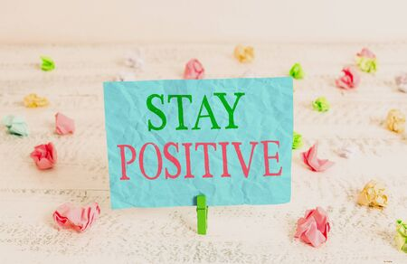 Word writing text Stay Positive. Business photo showcasing Engage in Uplifting Thoughts Be Optimistic and Real Green clothespin white wood background colored paper reminder office supply