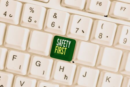 Handwriting text Safety First. Conceptual photo Avoid any unnecessary risk Live Safely Be Careful Pay attention White pc keyboard with empty note paper above white background key copy space