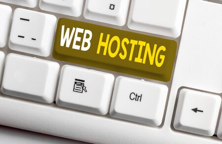 Conceptual hand writing showing Web Hosting. Concept meaning The activity of providing storage space and access for websites White pc keyboard with note paper above the white background