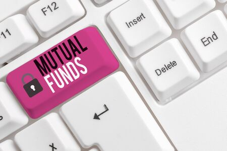 Conceptual hand writing showing Mutual Funds. Concept meaning An investment program funded by shareholders Individual Stocks White pc keyboard with note paper above the white background