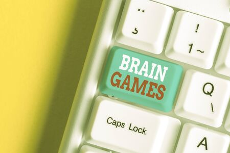 Writing note showing Brain Games. Business concept for psychological tactic to analysisipulate or intimidate with opponent White pc keyboard with note paper above the white background