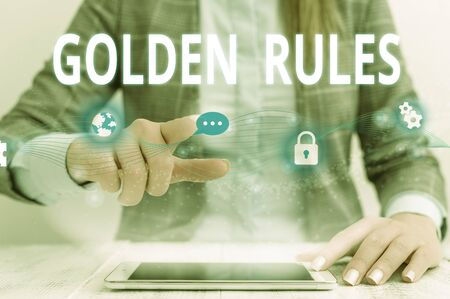 Writing note showing Golden Rules. Business concept for Basic principle that should be followed Important Principle Female human wear formal work suit presenting smart device Reklamní fotografie