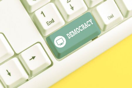 Text sign showing Democracy. Business photo showcasing freedom of the showing to express their feelings and beliefs White pc keyboard with empty note paper above white background key copy space