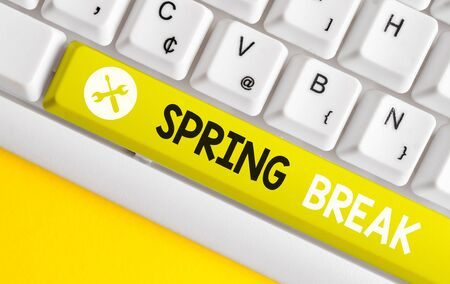 Conceptual hand writing showing Spring Break. Concept meaning Vacation period at school and universities during spring White pc keyboard with note paper above the white background