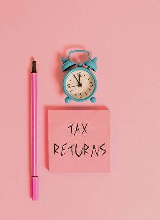 Text sign showing Tax Returns. Business photo text Tax payer financial information Tax Liability and Payment report Metal vintage alarm clock wakeup blank notepad marker colored background
