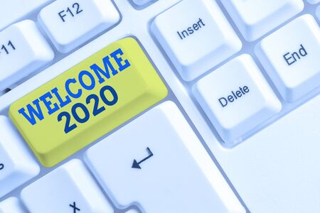Handwriting text Welcome 2020. Conceptual photo New Year Celebration Motivation to Start Cheers Congratulations White pc keyboard with empty note paper above white background key copy space