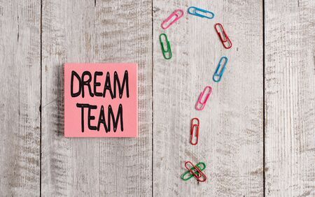 Writing note showing Dream Team. Business concept for Prefered unit or group that make the best out of a demonstrating Pastel colour note paper placed next to stationary above wooden table Stock Photo