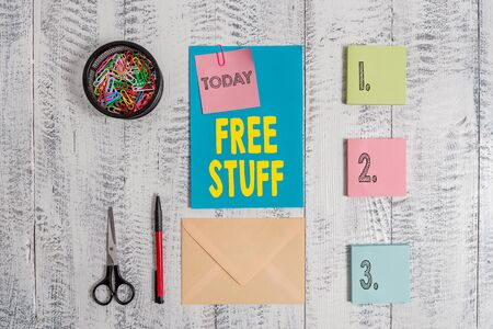 Word writing text Free Stuff. Business photo showcasing Any thing that you can have in a store that is not being paid Envelope letter sticky note ballpoint clips can scissors wooden background