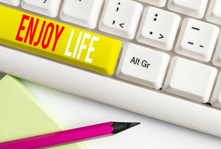 Handwriting text writing Enjoy Life. Conceptual photo Any thing, place,food or demonstrating, that makes you relax and happy White pc keyboard with empty note paper above white background key copy space Reklamní fotografie