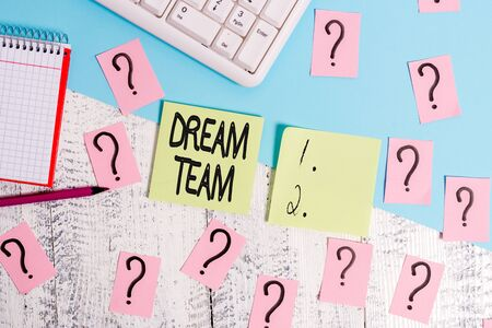 Conceptual hand writing showing Dream Team. Concept meaning Prefered unit or group that make the best out of a demonstrating Writing tools and scribbled paper on top of the wooden table