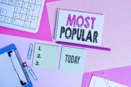 Text sign showing Most Popular. Business photo text Liked Followed Enjoyed by majority of the showing in a society Writing equipments and computer stuffs placed above colored plain table