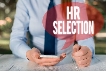 Writing note showing Hr Selection. Business concept for Process and approached by huanalysis resources when hiring employees Female business person sitting by table and holding mobile phone