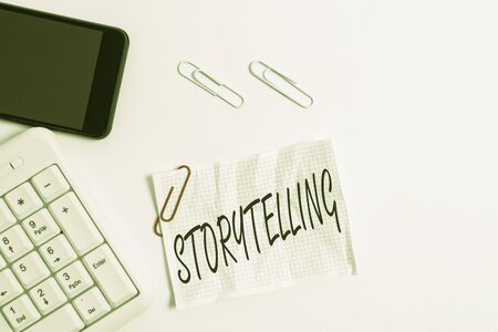 Text sign showing Storytelling. Business photo showcasing social and cultural Activity with Theatrical Gestures White pc keyboard with empty note paper above white background and mobile phone