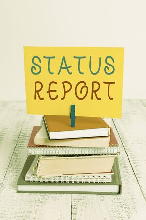 Conceptual hand writing showing Status Report. Concept meaning Update Summary of situations as of a period of time pile stacked books notebook pin color reminder white wooden
