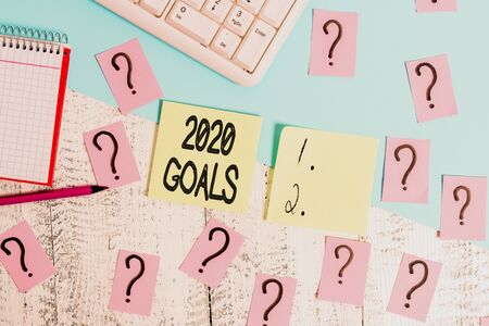 Conceptual hand writing showing 2020 Goals. Concept meaning A plan to do for something new and better for the coming year Writing tools and scribbled paper on top of the wooden table Stock Photo