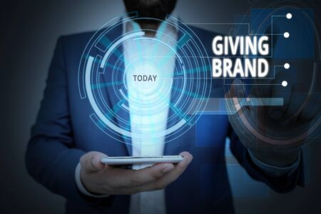 Conceptual hand writing showing Giving Brand. Concept meaning The process of giving a Name to a company products or services Male wear formal suit presenting presentation smart device 版權商用圖片