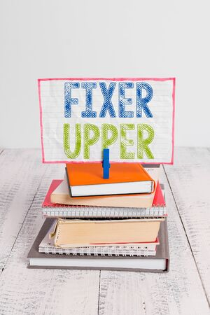 Word writing text Fixer Upper. Business photo showcasing house in need of repairs used chiefly connection with purchase pile stacked books notebook pin clothespin colored reminder white wooden Reklamní fotografie