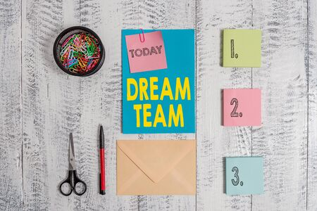 Word writing text Dream Team. Business photo showcasing Prefered unit or group that make the best out of a demonstrating Envelope letter sticky note ballpoint clips can scissors wooden background Stok Fotoğraf