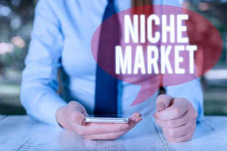 Writing note showing Niche Market. Business concept for Subset of the market on which specific product is focused Female business person sitting by table and holding mobile phone