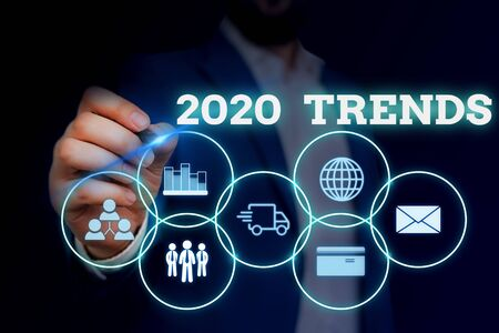 Handwriting text writing 2020 Trends. Conceptual photo things that is famous for short period of time in current year Male human wear formal work suit presenting presentation using smart device 스톡 콘텐츠