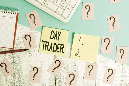 Conceptual hand writing showing Day Trader. Concept meaning A demonstrating that buy and sell financial instrument within the day Writing tools and scribbled paper on top of the wooden table