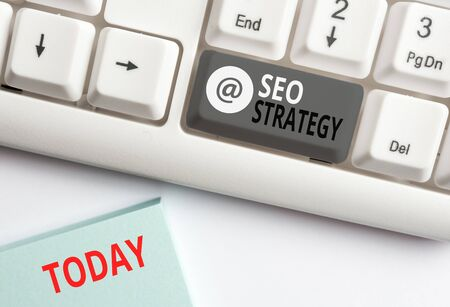 Word writing text Seo Strategy. Business photo showcasing Techniques and tactics to increase the visitors of a website White pc keyboard with empty note paper above white background key copy space