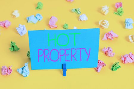 Writing note showing Hot Property. Business concept for Something which is sought after or is Heavily Deanalysisded Colored crumpled paper empty reminder white floor clothespin Foto de archivo