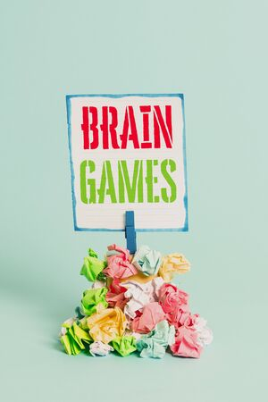 Word writing text Brain Games. Business photo showcasing psychological tactic to analysisipulate or intimidate with opponent Reminder pile colored crumpled paper clothespin reminder blue background