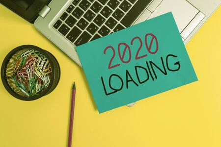 Word writing text 2020 Loading. Business photo showcasing Advertising the upcoming year Forecasting the future event Trendy metallic laptop small paper sheet pencil clips colored background