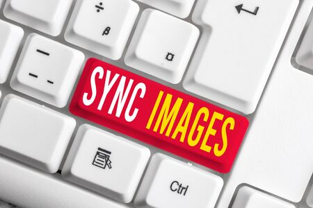 Handwriting text writing Sync Images. Conceptual photo Making photos identical in all devices Accessible anywhere White pc keyboard with empty note paper above white background key copy space