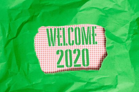 Text sign showing Welcome 2020. Business photo showcasing New Year Celebration Motivation to Start Cheers Congratulations Green crumpled ripped colored paper sheet centre torn colorful background