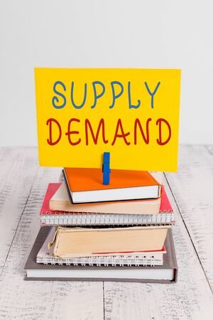 Conceptual hand writing showing Supply Deanalysisd. Concept meaning Relationship between the amounts available and wanted pile stacked books notebook pin color reminder white wooden