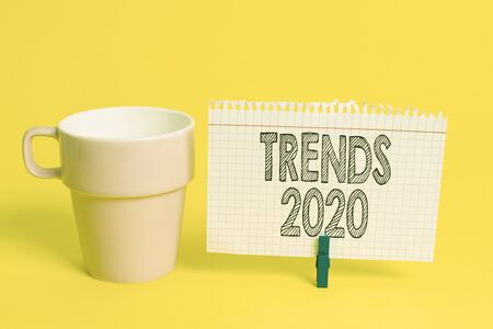 Writing note showing Trends 2020. Business concept for Upcoming year prevailing tendency Widely Discussed Online Cup empty paper blue clothespin rectangle shaped reminder yellow office Stock Photo