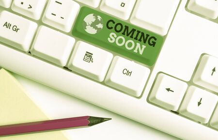 Writing note showing Coming Soon. Business concept for something is going to happen in really short time of period White pc keyboard with note paper above the white background