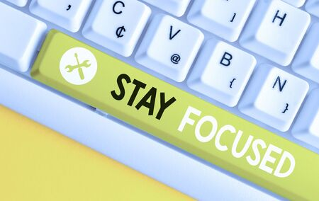 Conceptual hand writing showing Stay Focused. Concept meaning Be attentive Concentrate Prioritize the task Avoid distractions White pc keyboard with note paper above the white background Stok Fotoğraf