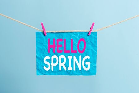 Writing note showing Hello Spring. Business concept for Welcoming the season after the winter Blossoming of flowers Clothesline clothespin rectangle shaped paper reminder white wood desk Фото со стока