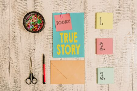 Word writing text True Story. Business photo showcasing The day to day experiences of an individual in his entire life Envelope letter sticky note ballpoint clips can scissors wooden background