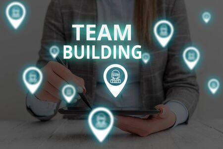 Text sign showing Team Building. Business photo text Types of activities used to enhance social relations Woman wear formal work suit presenting presentation using smart device Фото со стока