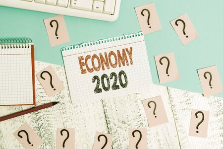 Text sign showing Economy 2020. Business photo showcasing State of wealth and resources of a country in upcoming year Writing tools, computer stuff and math book sheet on top of wooden table