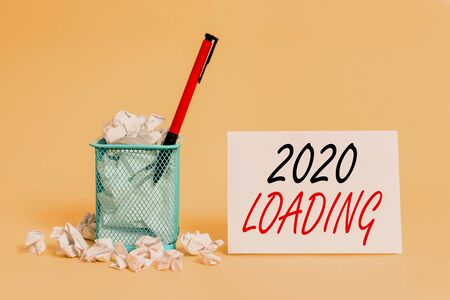 Text sign showing 2020 Loading. Business photo showcasing Advertising the upcoming year Forecasting the future event crumpled paper trash and stationary with note paper placed in the trash can