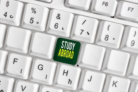 Handwriting text Study Abroad. Conceptual photo Pursuing educational opportunities in a foreign country White pc keyboard with empty note paper above white background key copy space Фото со стока - 130160147