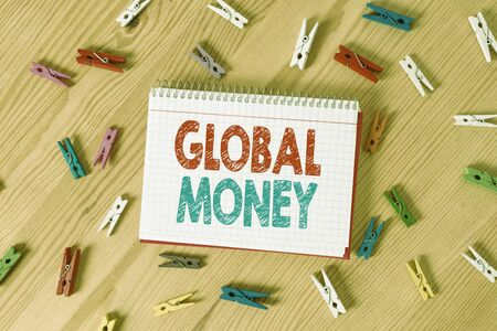 Conceptual hand writing showing Global Money. Concept meaning International finance World currency Transacted globally Colored crumpled papers wooden floor background clothespin